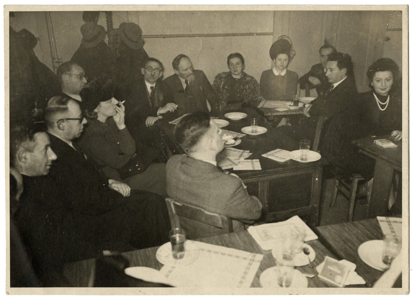 Meeting of a group of Belgian Jews.  [It is unclear if this is wartime or postwar.]  Among those pictured are Yitzchak Kubovitsky (third from left), Israel Tabakman (fifth from left facing camera with glasses), Nahum Pomerantz (third from right), Izak Szattan (second from right) and Fela Perelman at the far right.