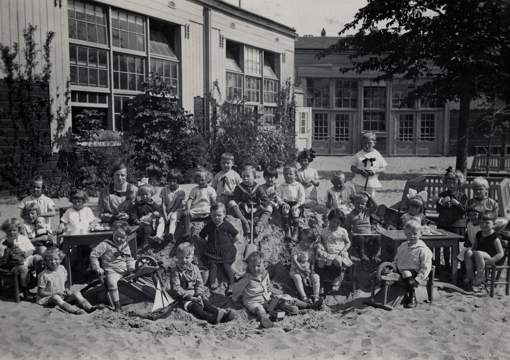 Young children play in a large sandbox in a kindergarten in Amsterdam.  Among those pictured is Betty Kok.