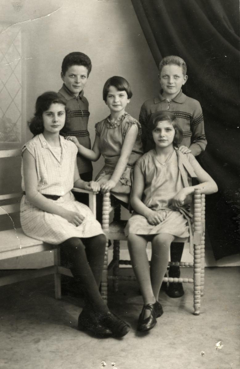 Studio portrait of the Kok and Vleeshouwer children, Dutch Jewish cousins.  From left to right are Ellie Bonn Vleeshouwer, Samuel Kok, Betty Kok, Jenny Bonn Vleeshouwer and Jacques Kok.  Only Betty and Elie survived.
