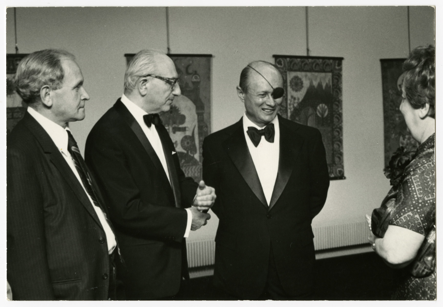 A group attends a reception in an art gallery.  Pictured are Chaim Perelman (second from the left) and Israeli General Moshe Dayan (third from the left).