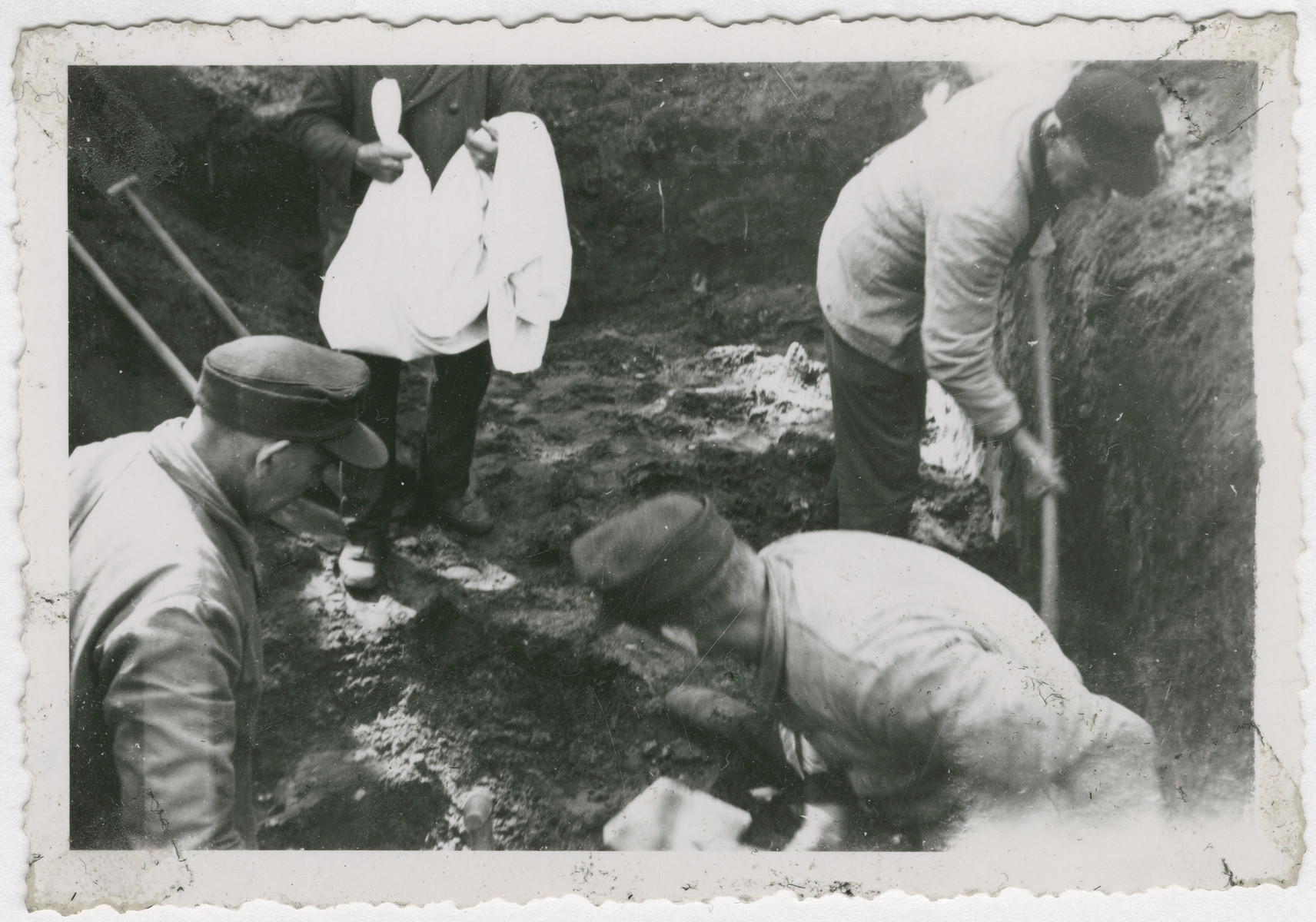 Corpses are exhumed for reburial from a mass grave in either the Buchenwald or Woebbelin concentration camp.