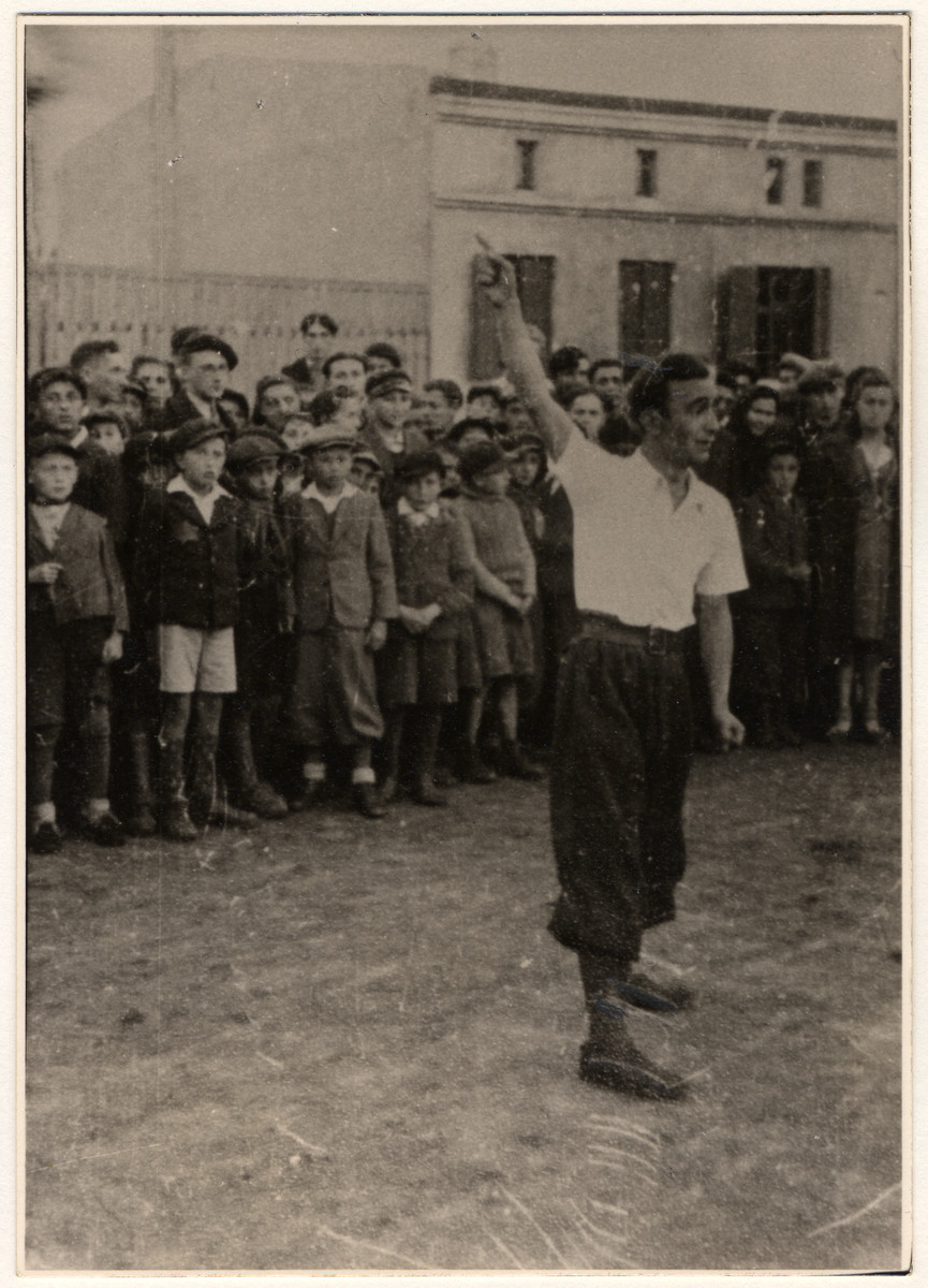 A crowd gathers aroung a street performer in the Lodz ghetto.