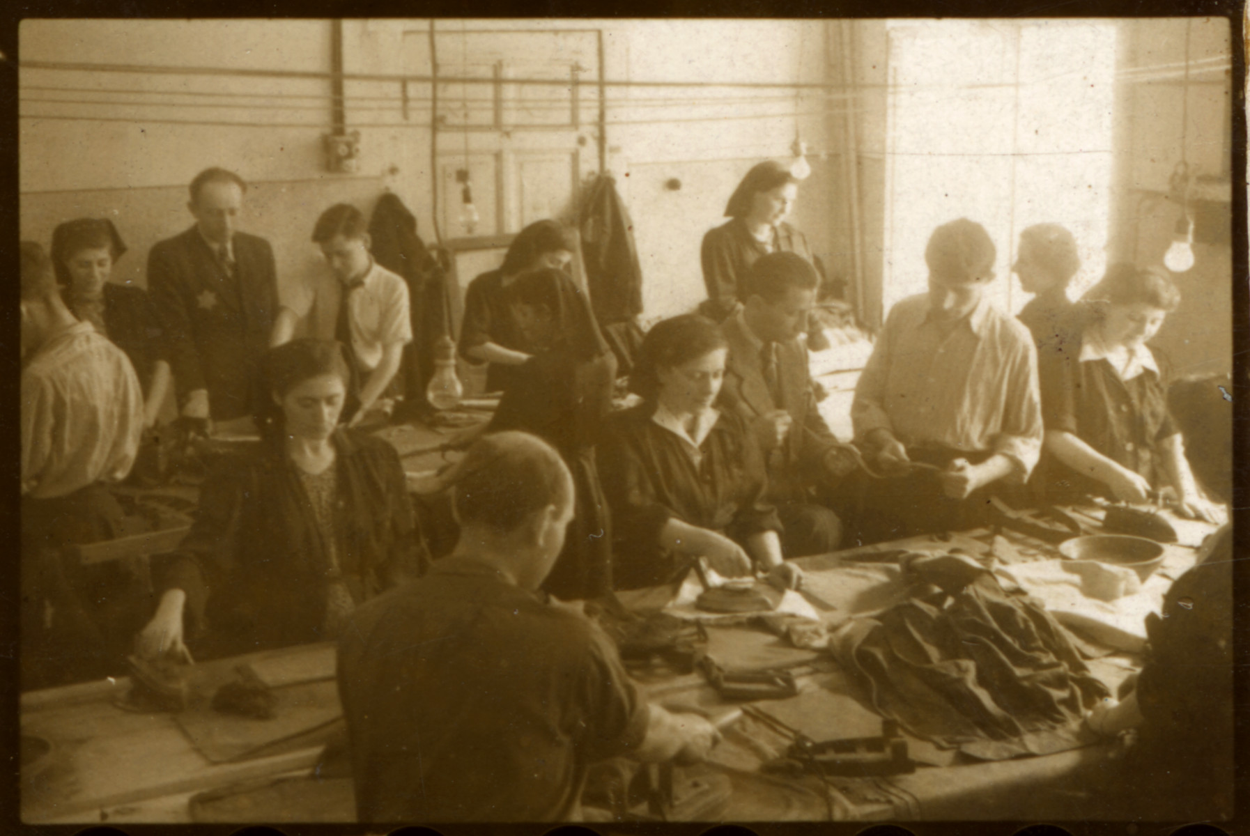 Workers iron and sew in one of the textile factory in the Lodz ghetto.