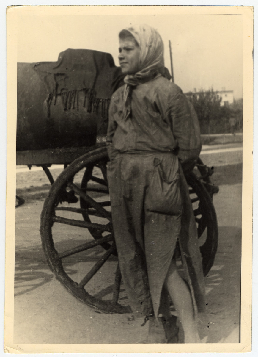 """Close-up photograph of a female """"fecalist"""", standing next to a sewage cart in the Lodz ghetto."""