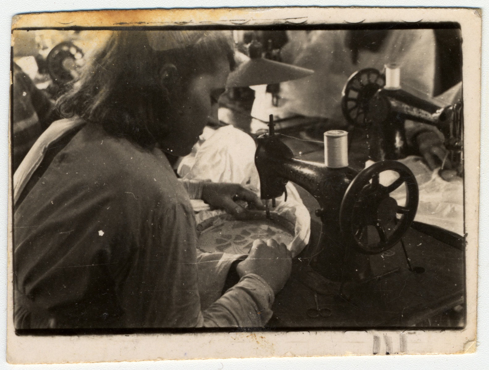 A Jewish woman does embroidery next to a sewing machine in a workshop in the Lodz ghetto.