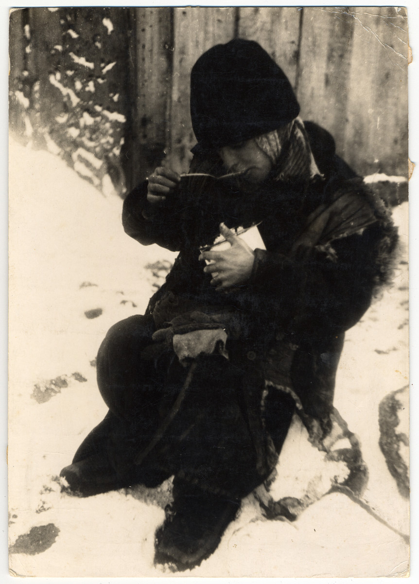 A destitute young boy in tattered clothes is eating his soup seated in the snow in the Lodz ghetto.
