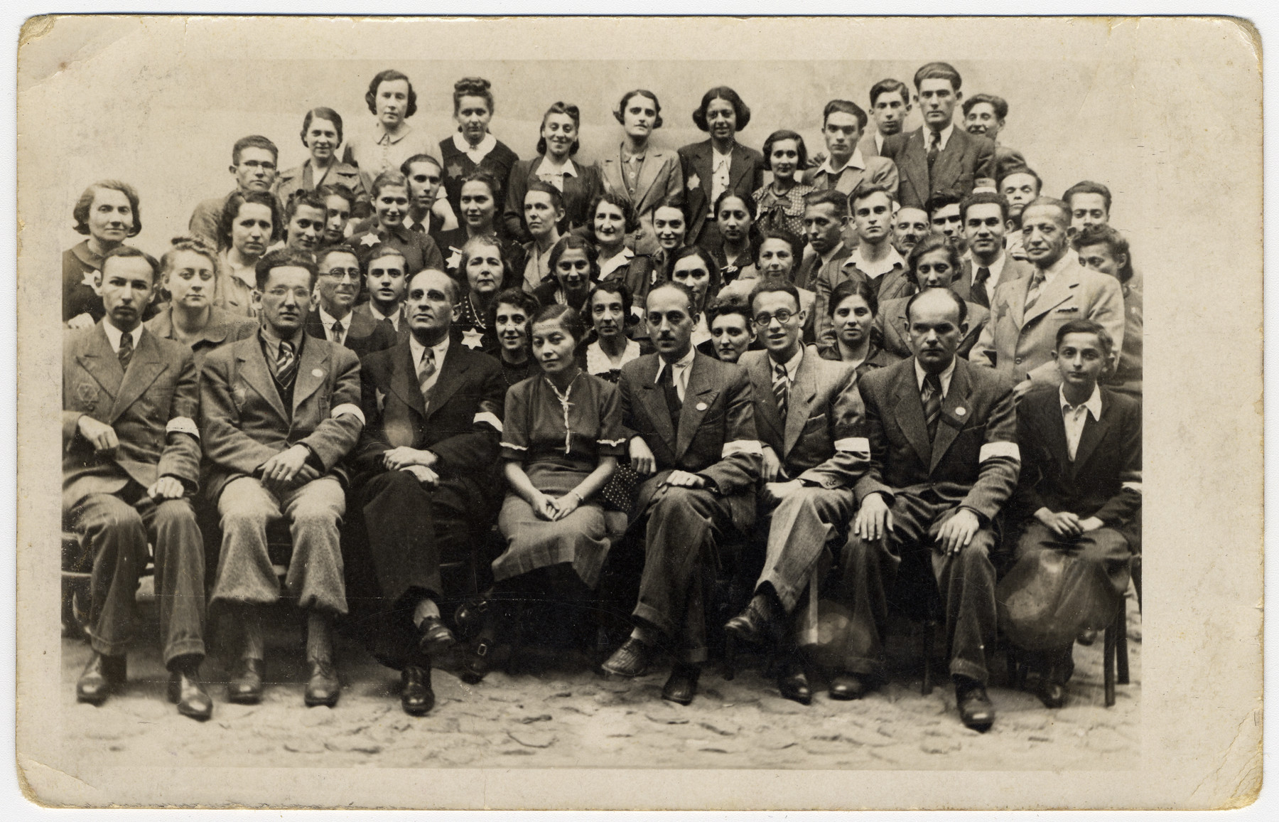 Group portrait of employees of the postal service in the Lodz ghetto.  Herbert Grabe, the head of the Post Office, is sitting third from the left in the front row.