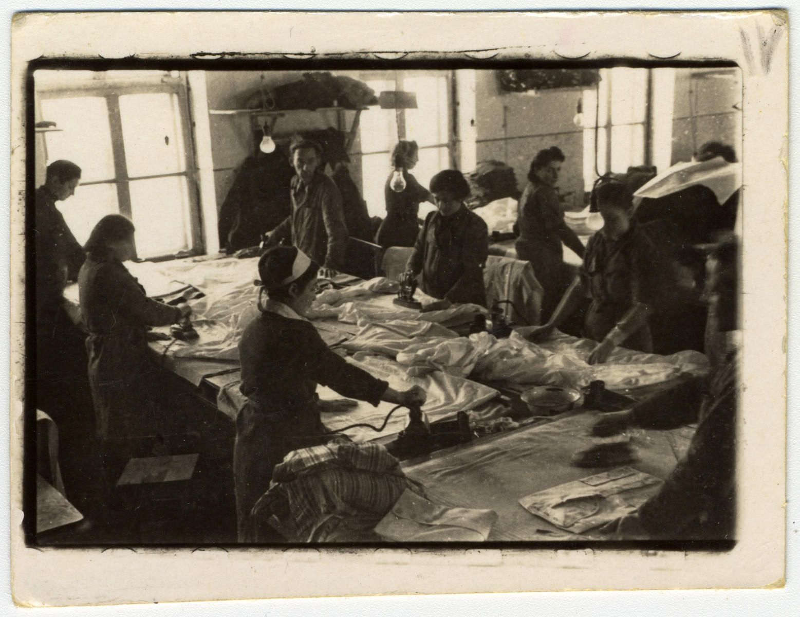 Jewish women iron sheets in either the laundry or a clothing factory in the Lodz ghetto.