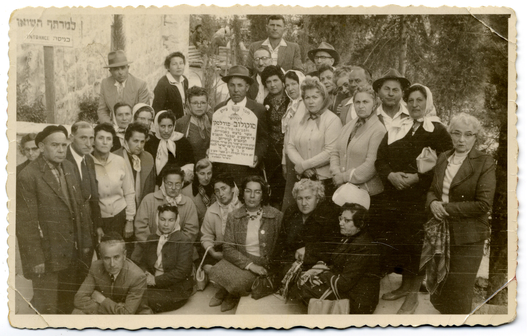 Survivors of Sokolow Podlaski pose around a makeshift tombstone during a memorial service for the Holocaust victims of the town.  Shoshana Feldman (sister of Mendel) is among those pictured.  She immigrated to Palestine before the war is part of the group.  Also pictured is Srul Szczerb, seen  holding the plaque. His sister, Malka  (Szczerb) Goldschmidt  is standing to his right (wearing a scarf and glasses). The two survived the war in Russia and then immigrated to Israel afterwards.  Their younger sister, Cywia (Szczerb) Elster, had been hiding in the farms around the town of Sokolow and was turned in to the Germans by a farmer named Oziemblo six months before the end of the war. The Germans brought her into the town and then shot her. Cywia's children,  Irene  and Aaron Elster survived.