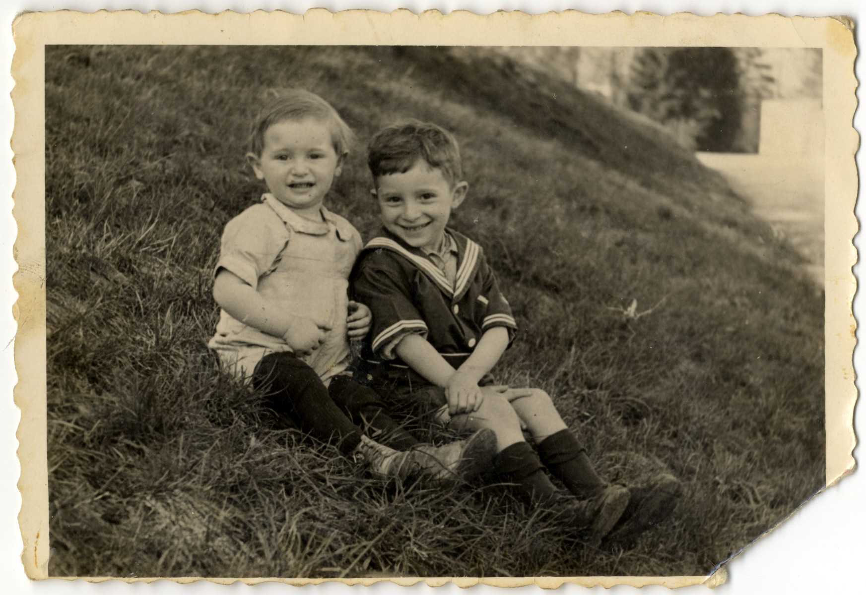 Irving and Fred Feldman sit on a grassy hill in the Wels displaced persons' camp.