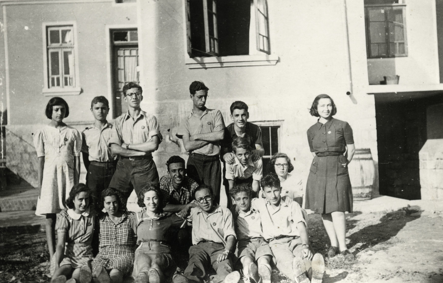 Group portrait of Jewish youth [probably either a school group or Betar] stand outside a building wearing Jewish stars.  Among those pictured are Katia and Maria Gurewitz (right side) and Moshe Ben Aroya.