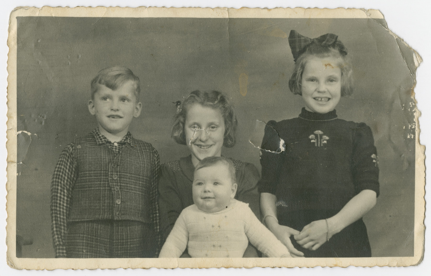 Aaron Jedwab, a Jewish infant in hiding as Jan Willem Herfstein, poses with his foster siblings Dick, Janni and Ina Wikkerink.