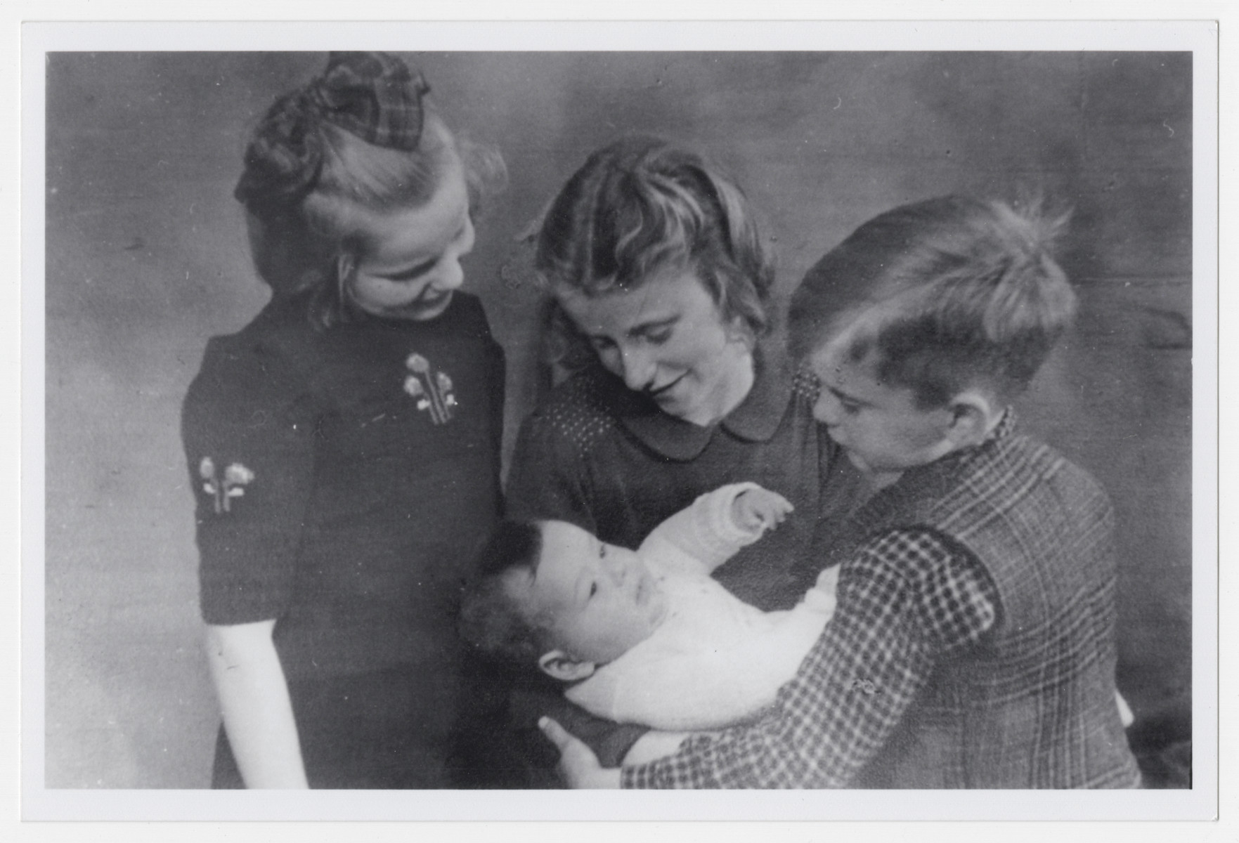 Aaron Jedwab, a Jewish infant in hiding as Jan Willem Herfstein, is cradled by his foster siblings Dick, Janni and Ina Wikkerink.