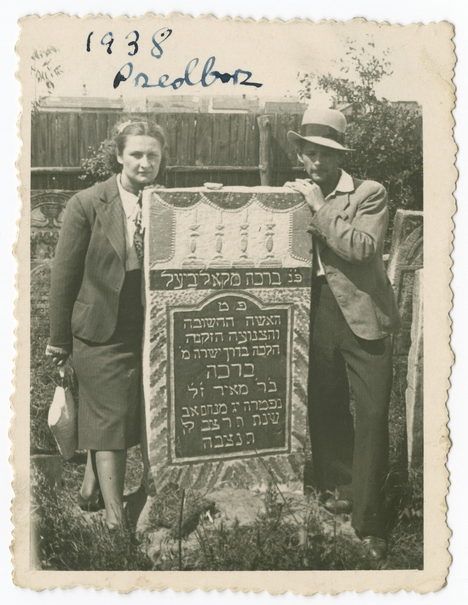 Two family members pose next to the grave of Bracha the daughter of Meir, a member of the Kodzidlo or Herszlikowicz family.  Pictured are Gussie and Srul, an uncle of Hanna.
