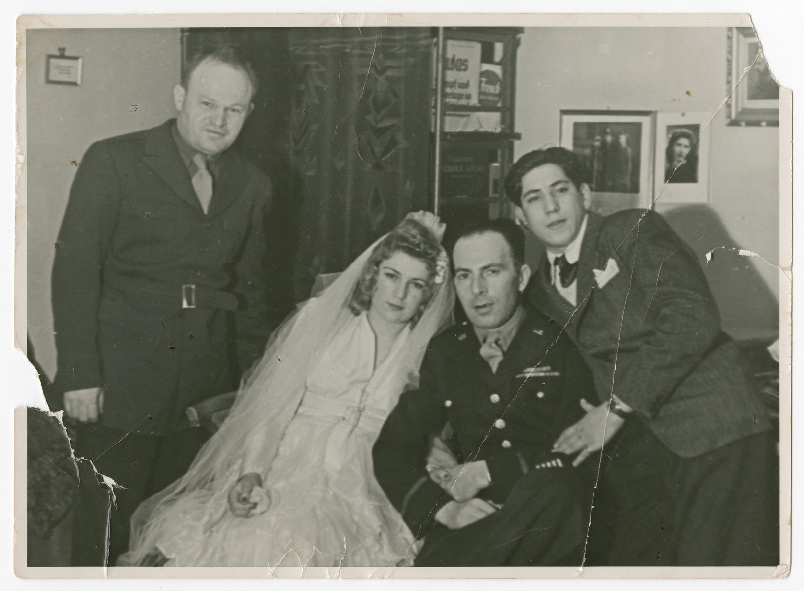 David Eizenberg (left) poses with the bride and groom at the wedding of a displaced person with an American soldier, probably in Berlin.