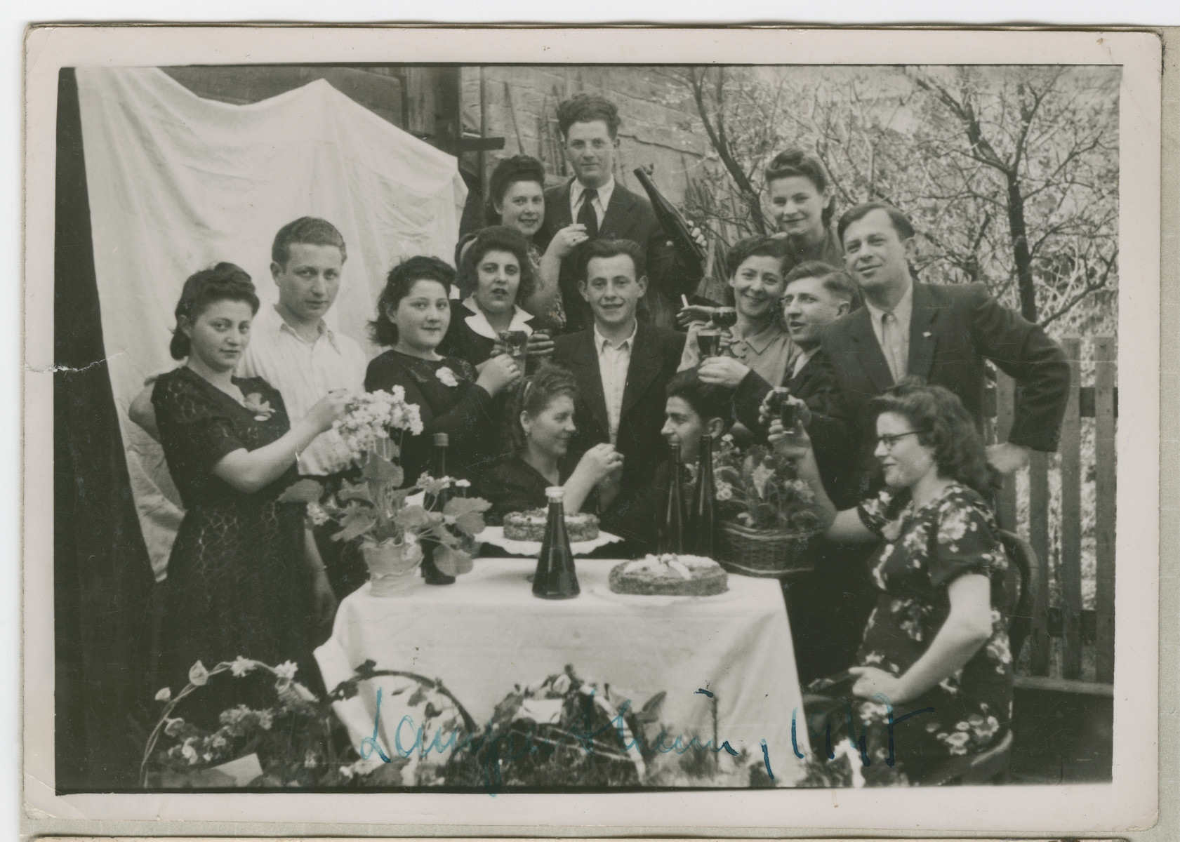 A large group of men and women raises glasses in a celebration in the Lampertheim displaced persons camp.  Pictured on the left are Regina and David Kadzidlo.