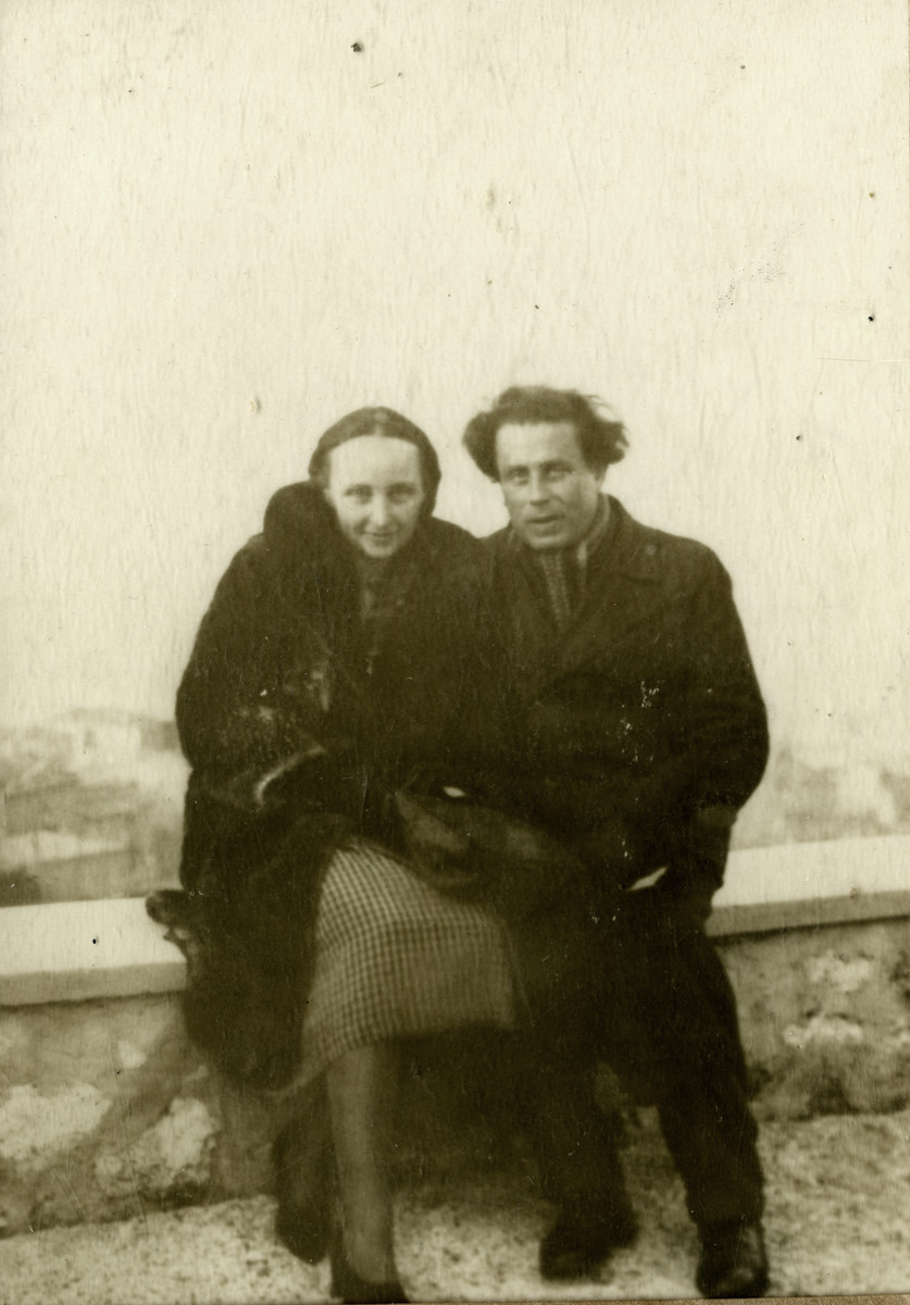 Victor Tulman and Hella Bacmeister, both internees in Gurs, rest on a ledge while on an outing in Marseilles.
