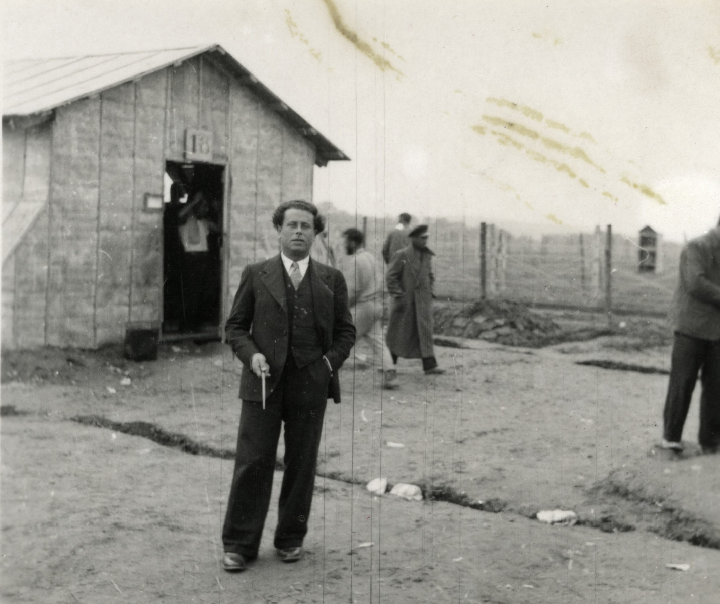 Rabbi Victor Tulman poses in front of a barracks in Gurs while Spanish internees work in the background.  This photograph was taken in the early days of the camp while it was still under construction.