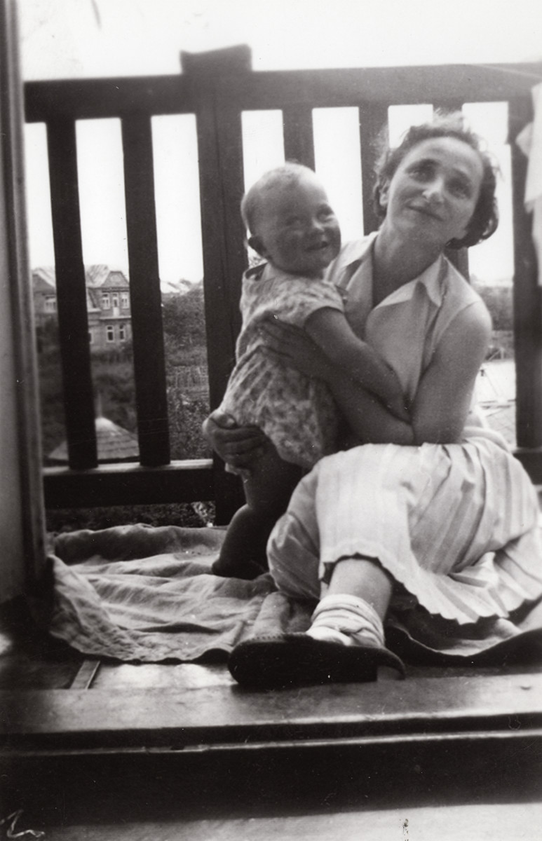Leah Kaplan holds her baby son Shalom on the balcony of their apartment.