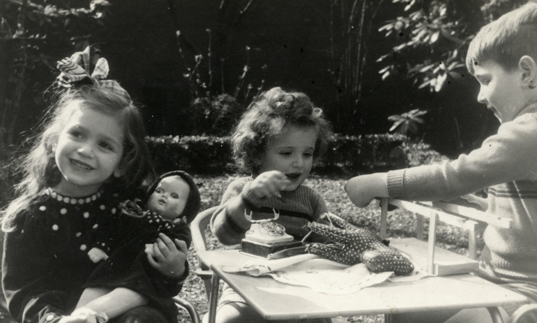 The Eisenmann children play in their garden of their home in Amsterdam prior to going into hiding.  Pictured are Ruth, David and Gershon Eisenmann.