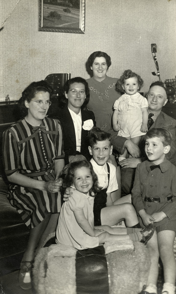 An extended Dutch Jewish family gathers in the living room of their apaprtment prior to going into hiding.  Seated in front is Ruth Eisenmann, her cousin Lex Aronson and her brother Gershon.  Her father, Shmuel Eisenmann, holds her younger brother David on the right.  Her mother Henne is standingin the center, and her mother's two sisters are seated on the left.