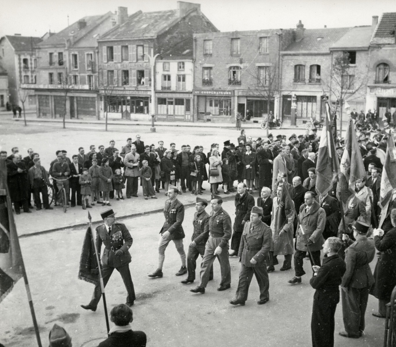 Members of the Free French Forces parade through the streets of a French town.  Victor David Tulman is pictured marching in the front row on the right.