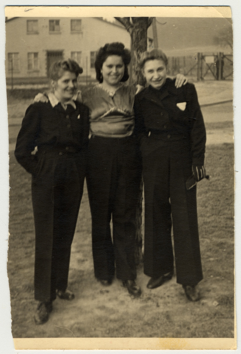 Irena Wojcik poses with two friends in factory uniforms in either the  Aschaffenberg or Wildflecken displaced persons camp.