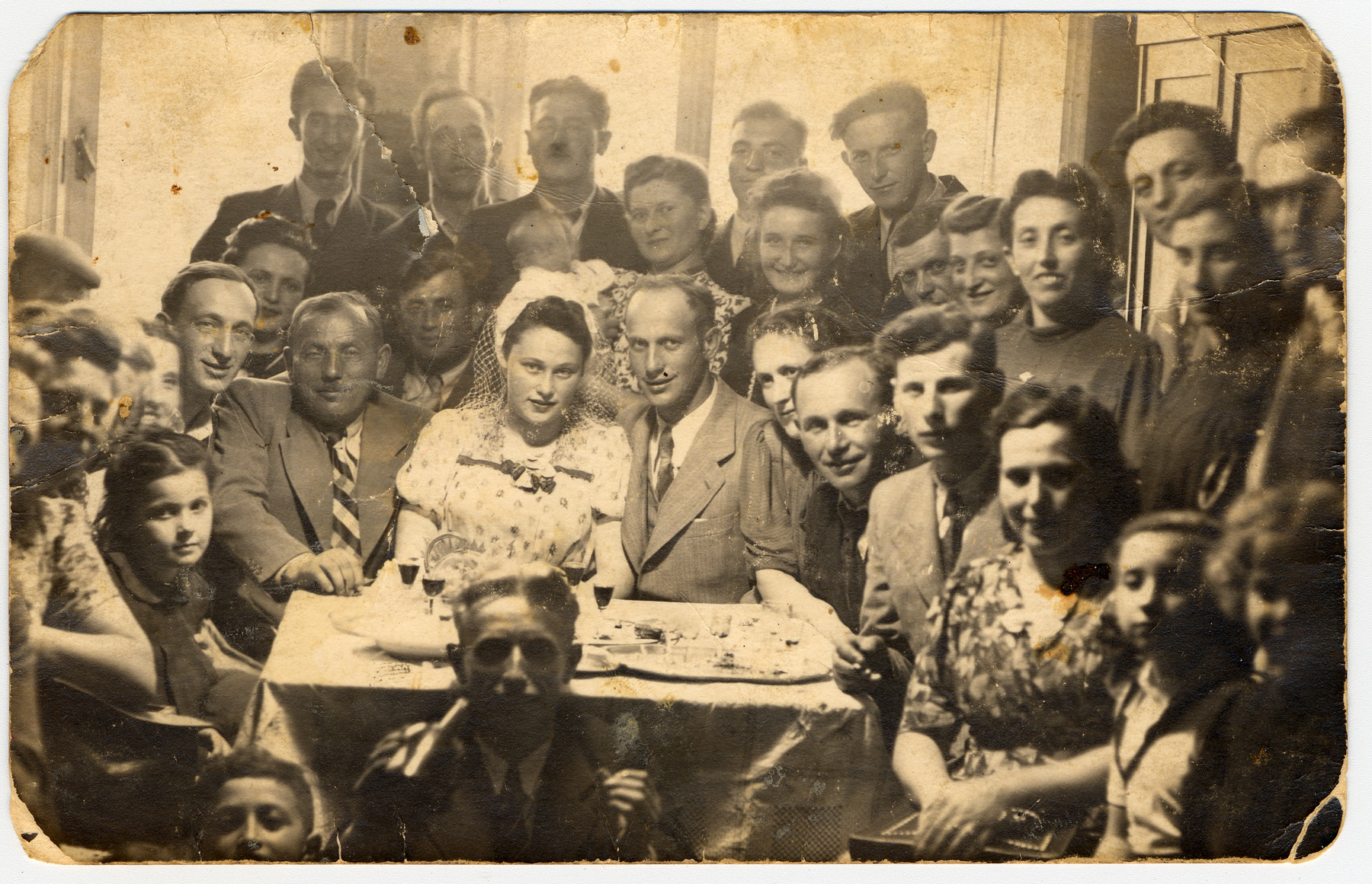 A group of friends gather for a celebration [possibly a wedding] in the Deggendorf displaced persons' camp.  Among those pictured are Moses and Mania Leinwand (second row, sixth and seventh from the right).