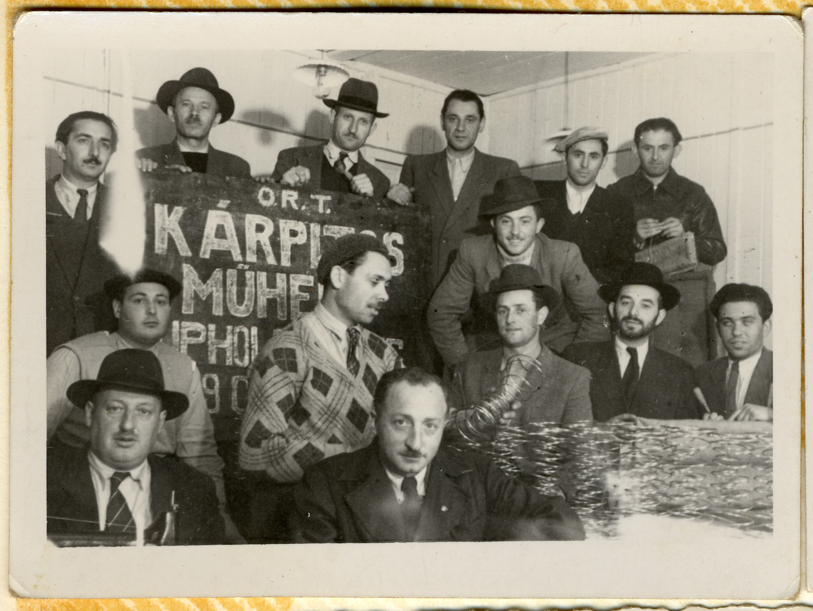 Jewish men in an ORT vocational school in the Hallein displaced persons' camp pose next to a display of mattress springs.