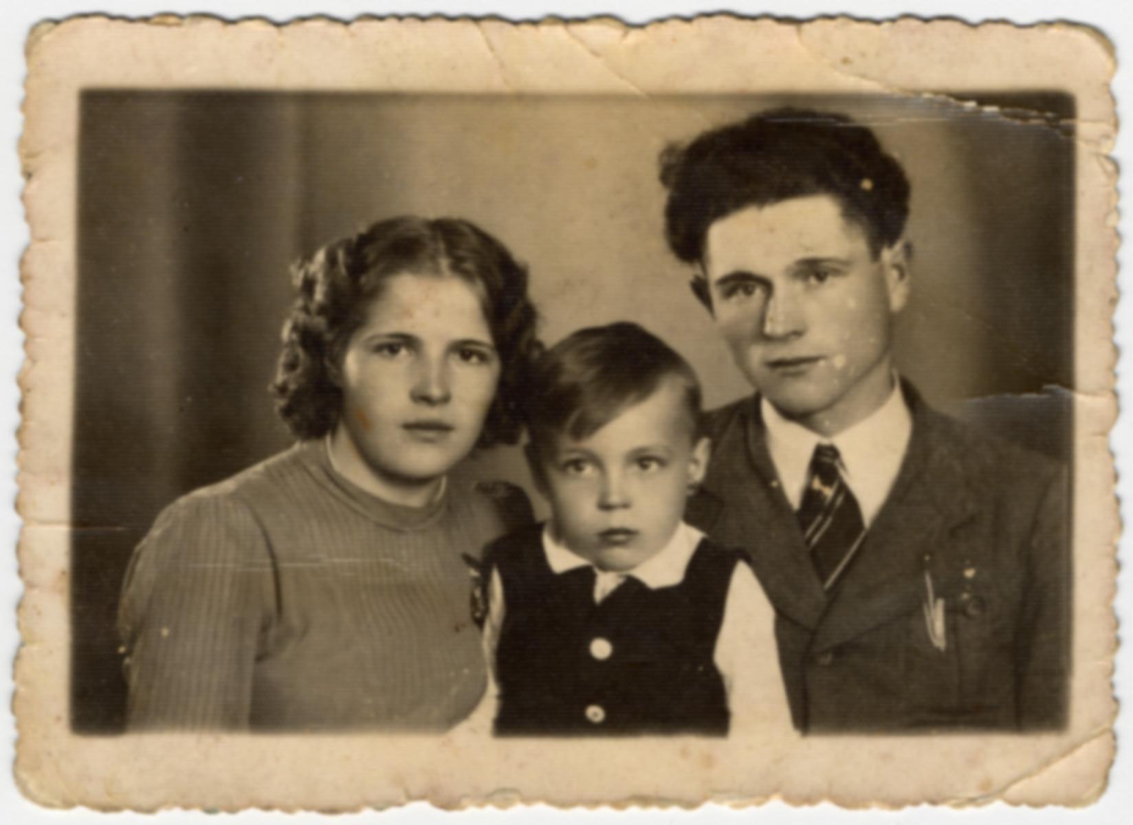 Studio portrait of Irena Wojcik,  her nephew, Henryk Szymczyk, and her pre-war fiance.