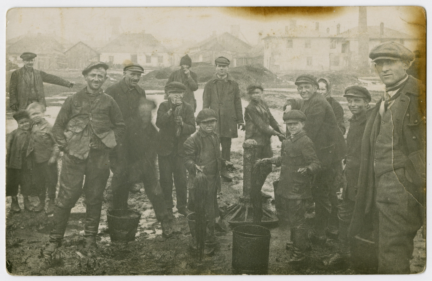 Men and boys gather by a water pump in the main square [probably of Borislav.]