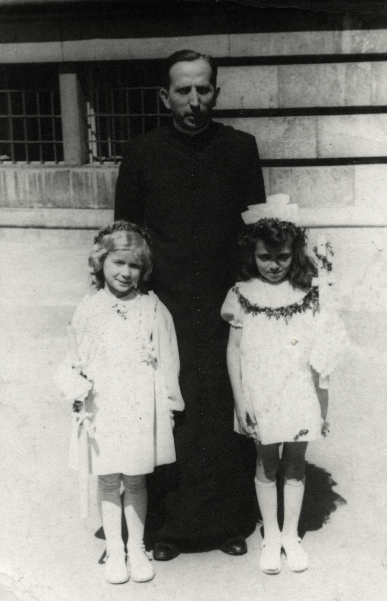 Janina Nebel (right), a Jewish child stands with a priest and another child after her First Communion.
