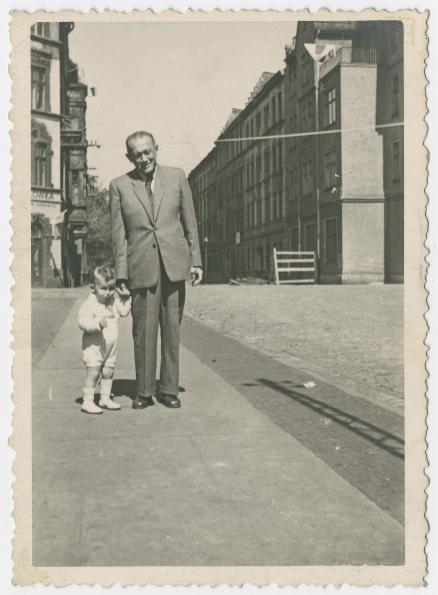 Stefan Burg walks down a street in Gleiwitz holding the hand of [his father].