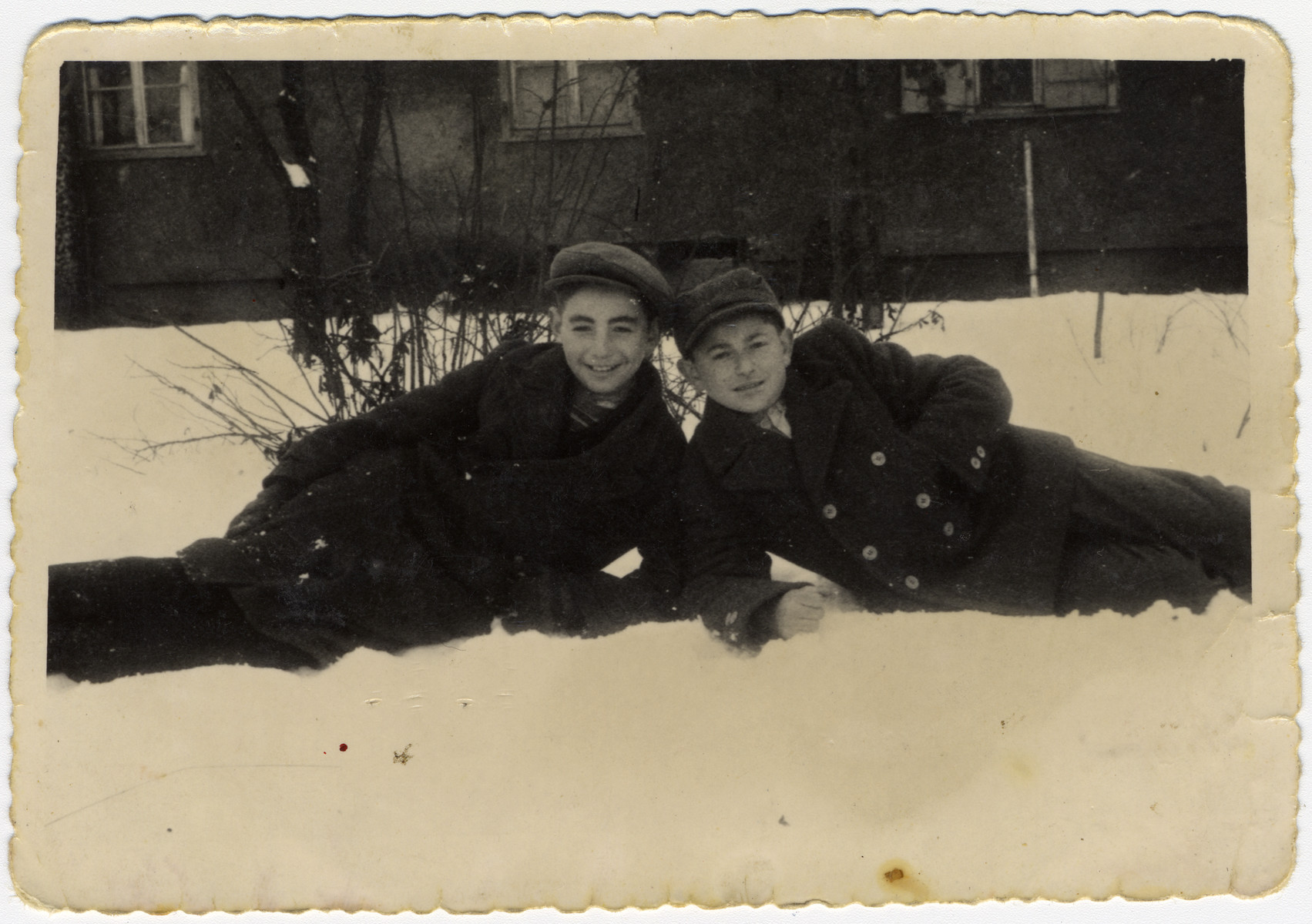 Two teenagers lie in the snow in the Pocking displaced persons' camp.  Zvi Hirsh Brill is on the right.
