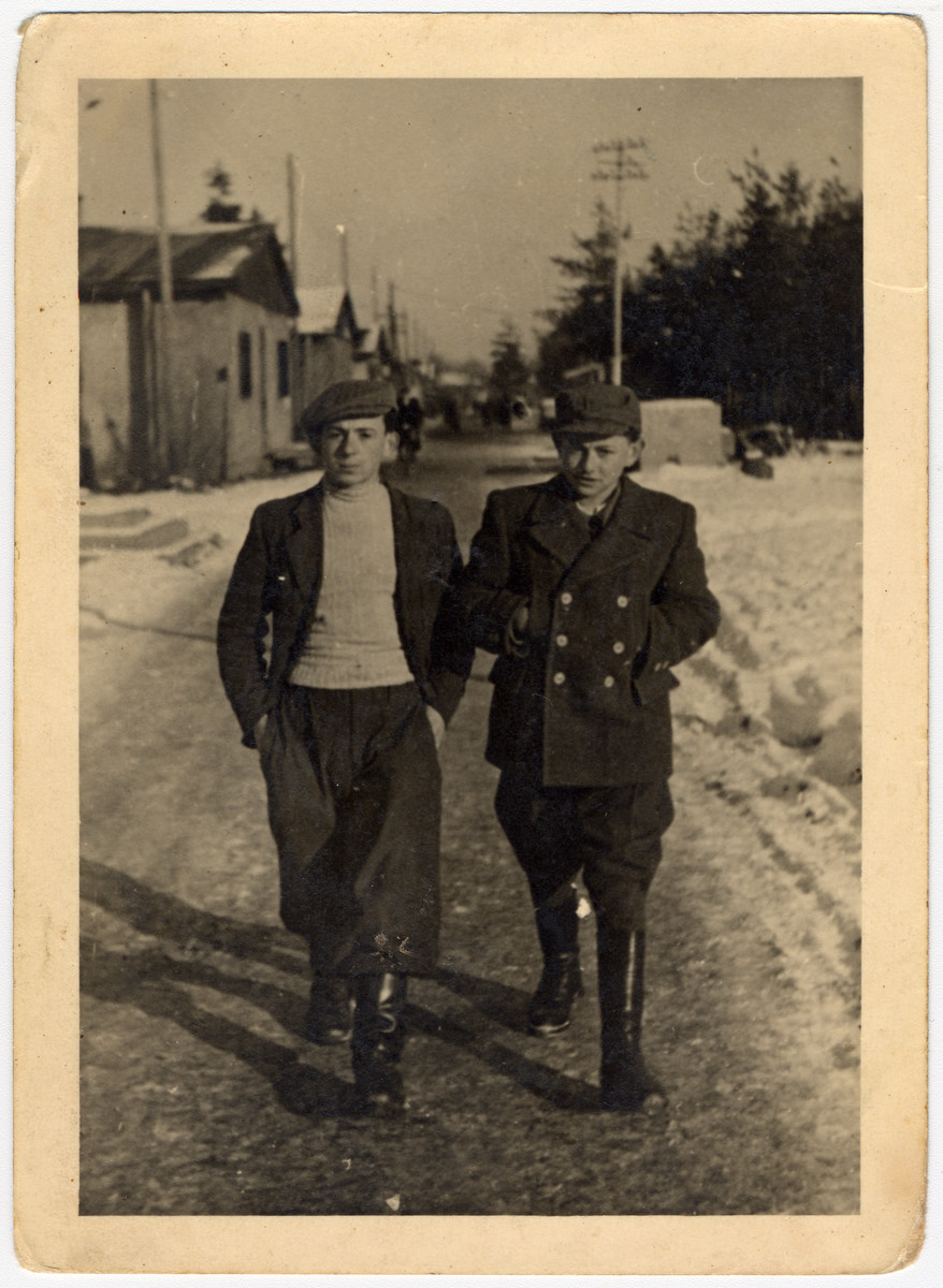 Two teenagers walk through a snowy street in the Pocking displaced persons' camp.  Zvi Hirsh Brill is on the right.