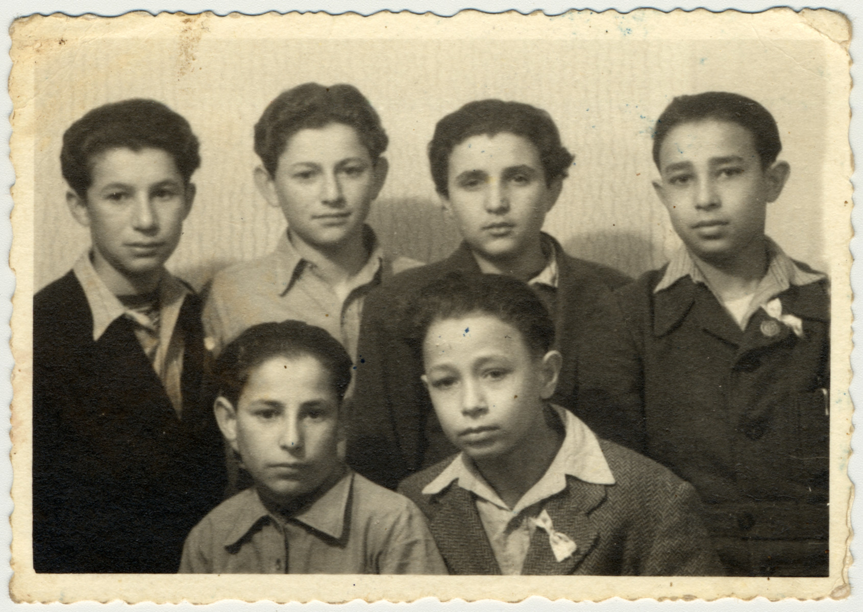 Studio portrait of a group of teenagers in the Rosenheim displaced persons' camp.  Pictured in the back row from left to right are Motle Goldfinger, Tzvi Brill, unknown, Aaron Miller.  Seated in front of Aaron Miller is his brother.