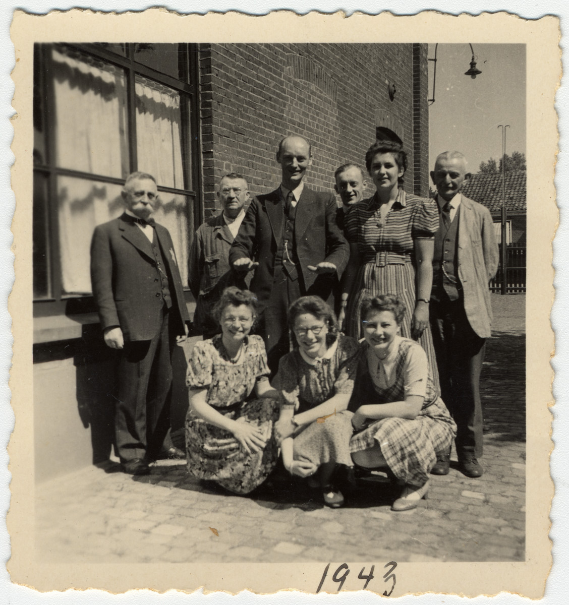 "A Jewish businessman poses with the workers in his textile factory ""M. van Dam and Zonen"" on his last day before he was forced to hand over his business.  Isidoor zan Dam is pictured on the far left wearing a yellow star."