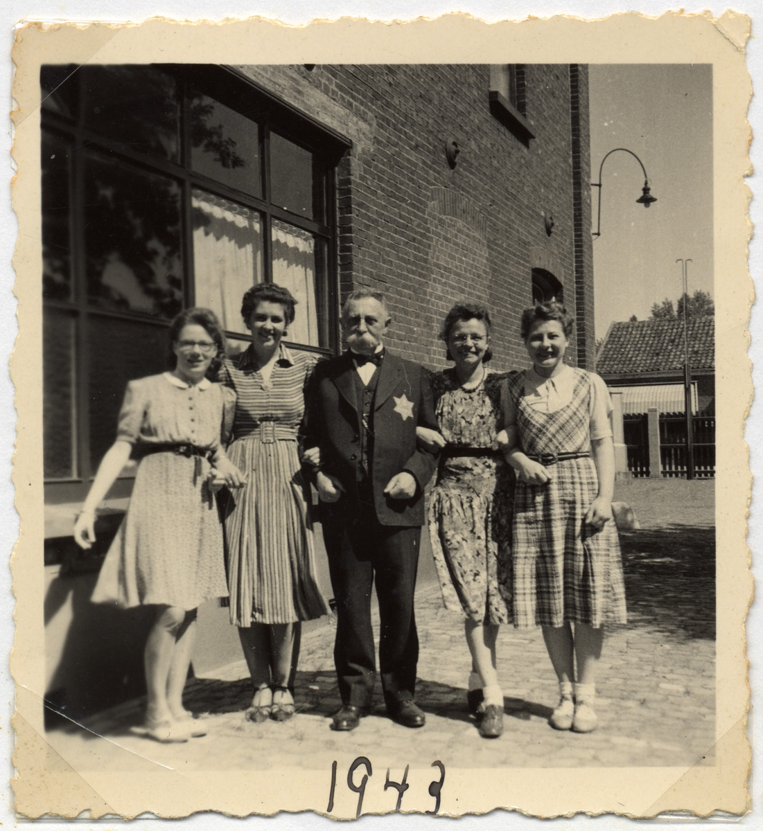 "A Jewish businessman poses with the workers in his textile factory ""M. van Dam and Zonen"" on his last day before he was forced to hand over his business.  Isidoor zan Dam is pictured wearing a yellow star."