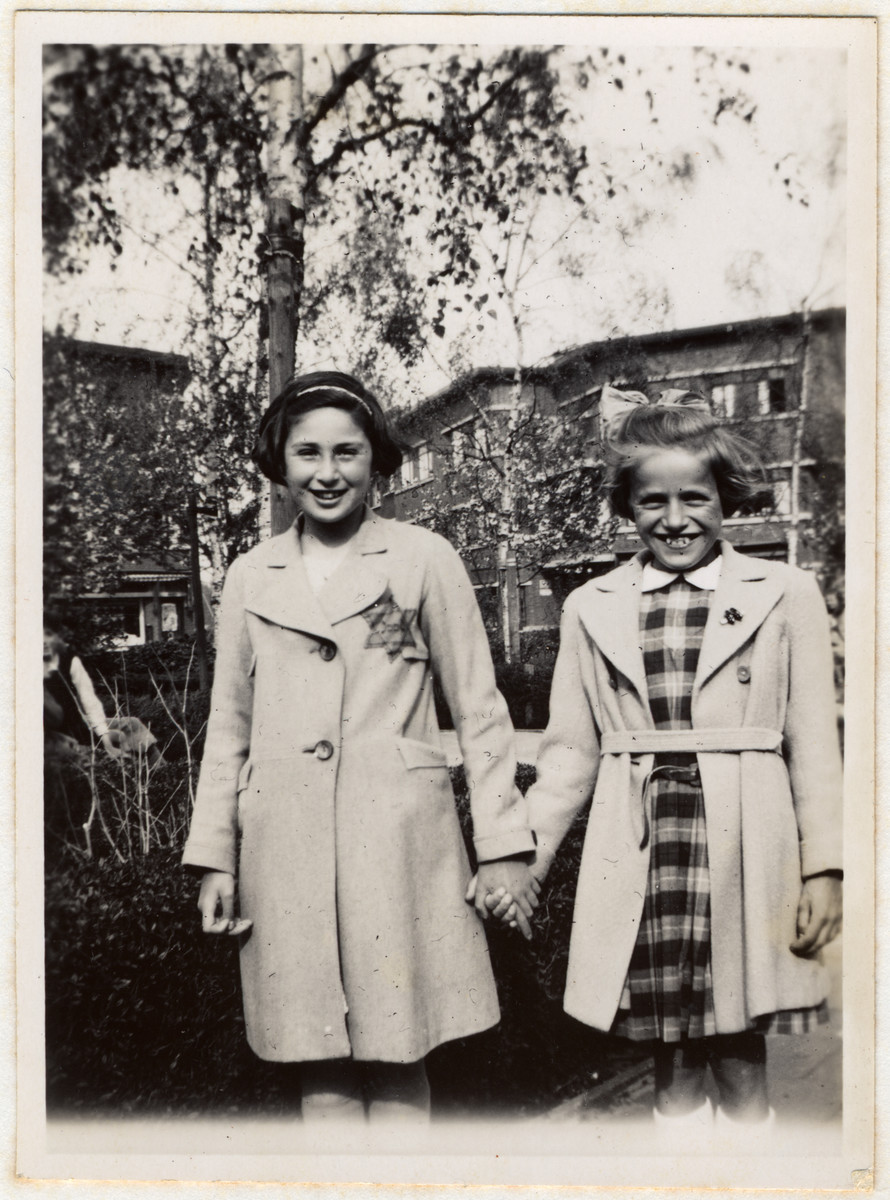 Close-up portrait of Clary van Dam, a young Dutch Jewish girl, wearing a Jewish star holding hands with a Christian friend.
