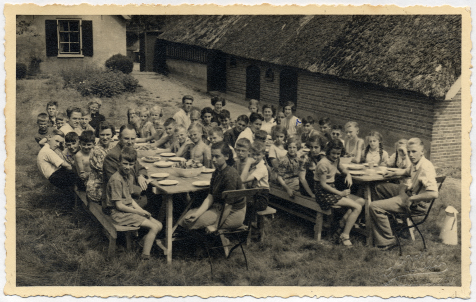 Dutch Jewish children gather around two picnic tables in a summer school camp in The Netherlands.