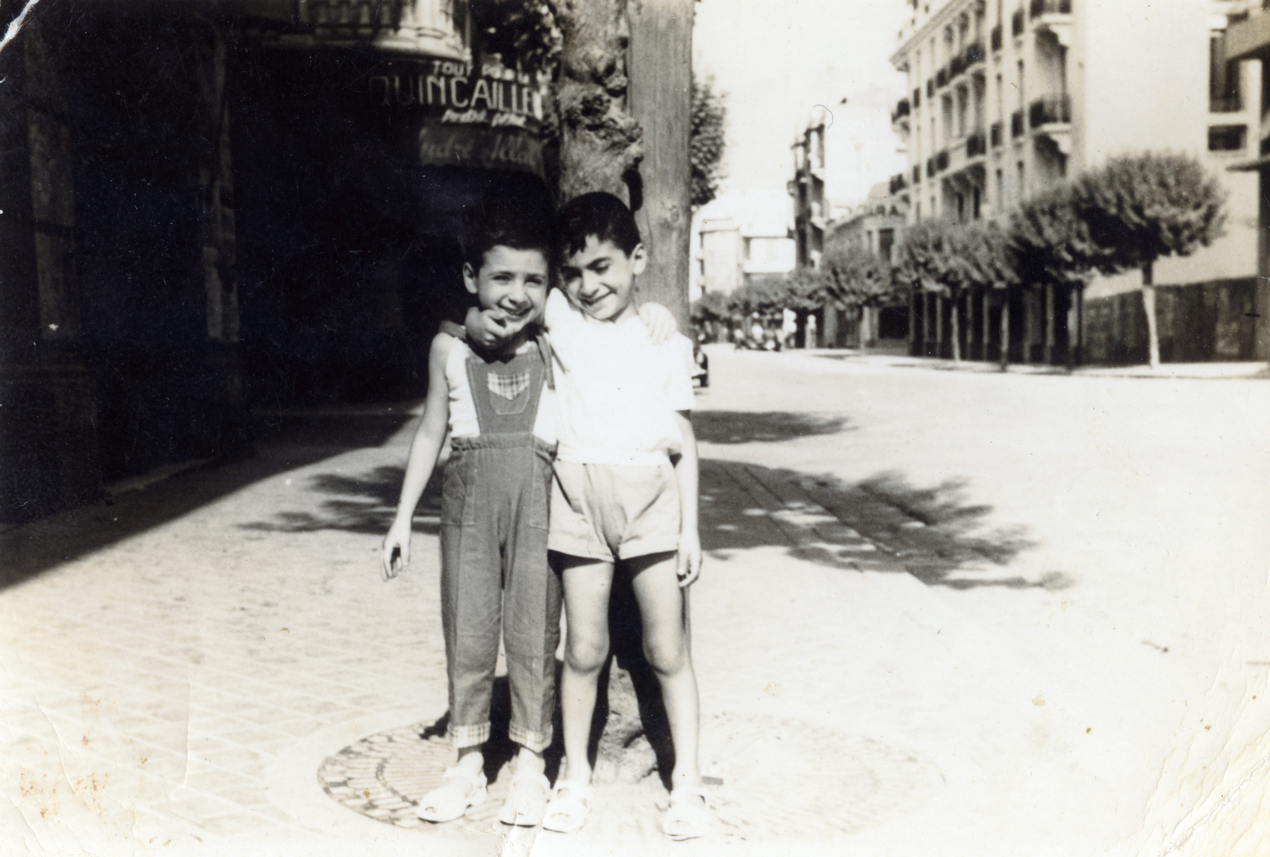 Ronnie and Ely Khayat standi outside on their street in Tunis the day before they immigrated to Israel.   Their house can be seen behind them in the background.