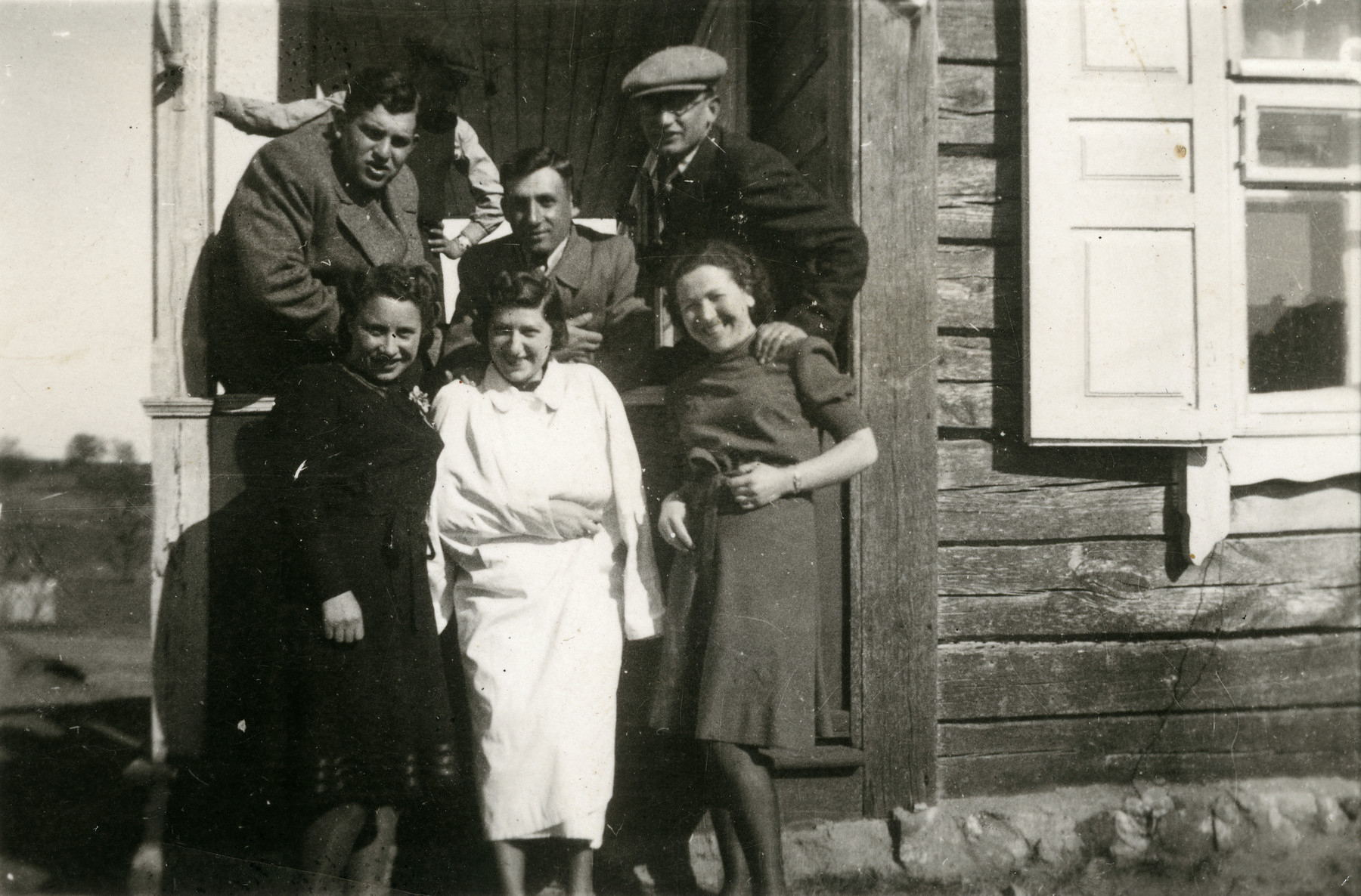 Rachel Godroff, wearing a white coat in the center, with friends in front of their house in Vievis in 1940.