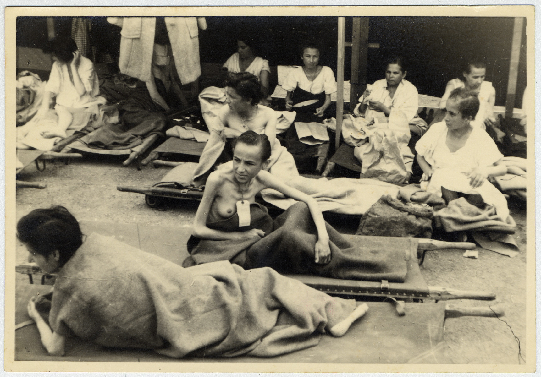Female Bergen-Belsen survivors rest on stretchers.