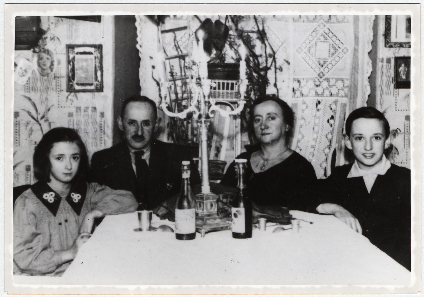 The Megdal family sits around a Sabbath table with challah, wine and candles shortly before the start of World War II.  Pictured from left to right are Perla, Behr-Efraim Dov, Brucha and Meyer Megdal.