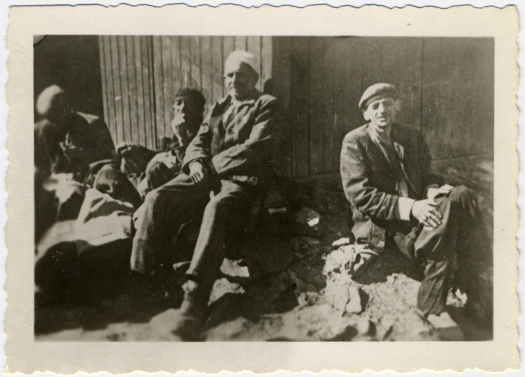 Four survivors rest outside a barracks in the Dachau concentration camp.