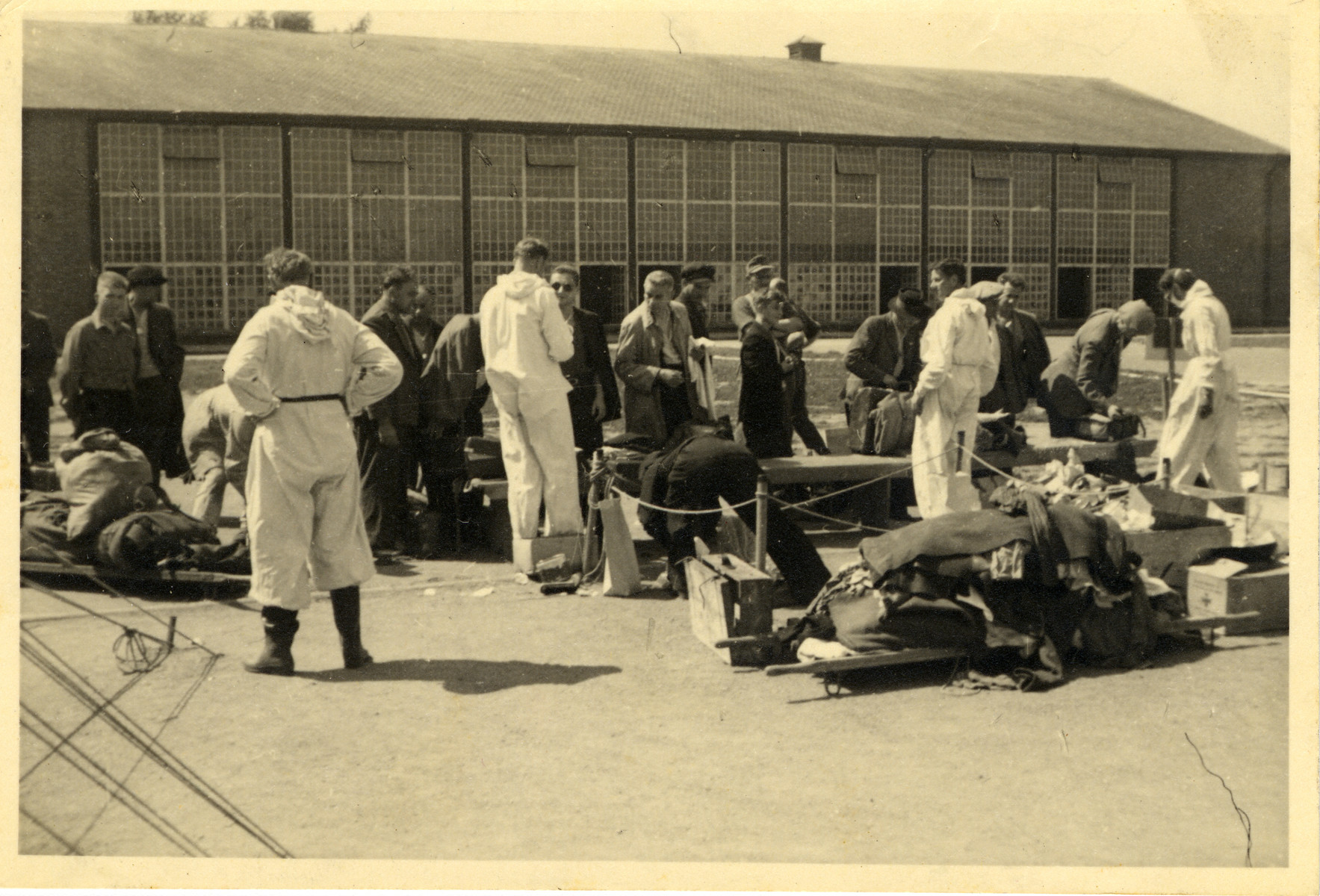 A group of men line up outside a building; they are being attended by five men dressed in white overalls.  On the floor are cardboard boxes, a suitcase, and two stretchers covered with clothes.