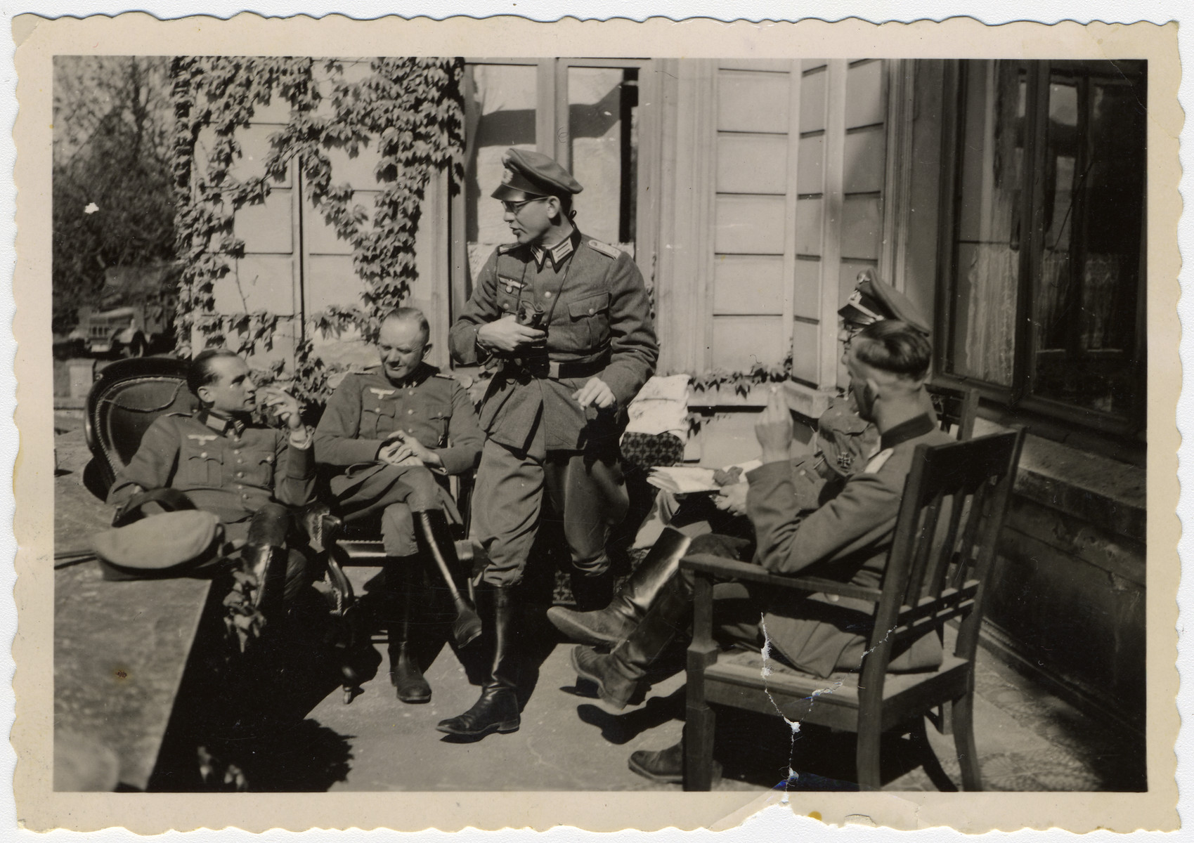 A group or German soldiers relaxes outside a home in Paris.  On the far left is Bernhard Kullak, a German army physician.
