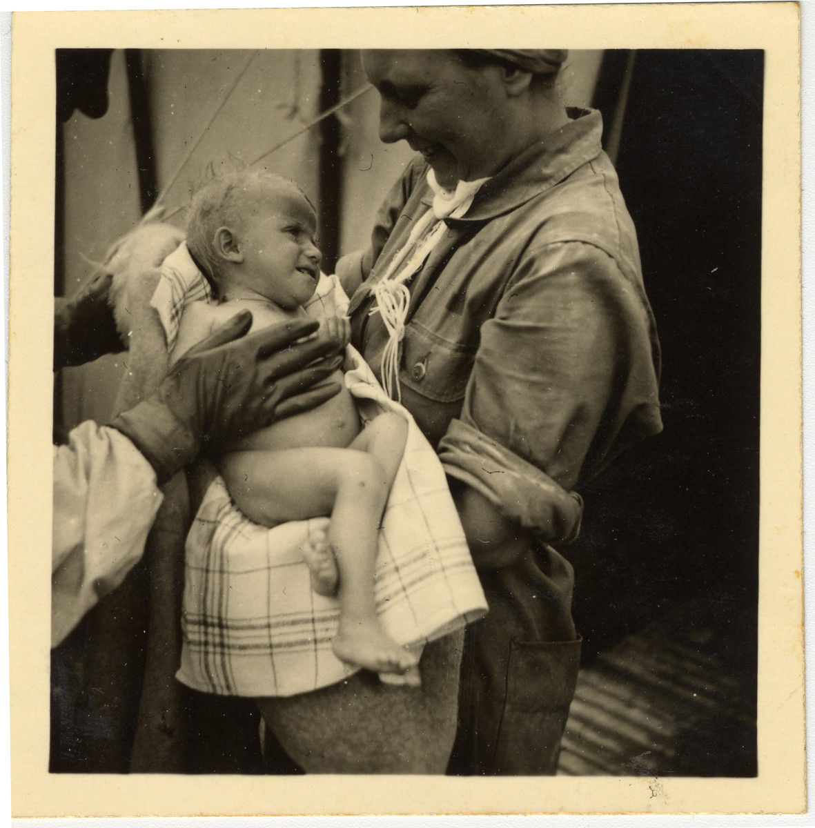 A woman holds a child suffering from cigarette burns while a doctor attends to him.