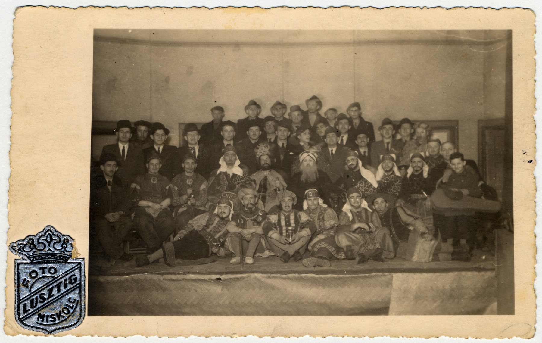"Hungarian Jewish survivors perform the ldrama with incidental music ""Yosefspiel"" (The Legend of Joseph).  Among those pictured are second row, seated: 4th from left, William (Bela) Rosenthal, Moishe Shoenfeld, Jeno (Yaakov) Rosenthal.  Third row: far left Zoli Reisman, (to left of man in beret) then in hat, Pali (Paul) Reisman, Imi Reisman, the young boy over Jeno Rosenthal (seated with turban) is Alexander (Sanyi) Reisman, to his right, head at an angle with moustache Arthur Rosenthal; and Bela Reisman (wearing a hat, second from the right).  According to the aunt of the donor this photo might have been taken between 1941 and 1944."