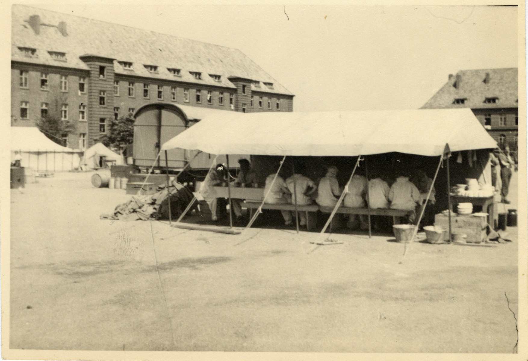 A group of people gather for a meal under a tent in Luebeck.